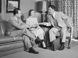 Couple Sitting on Couch Talking to Smiling Insurance Salesman Handing Them a Policy Photographic Print by H. Armstrong Roberts
