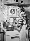 1950s Housewife Wearing Checkered Dress Standing in Kitchen Stirring Pot on Stove Photographic Print by H. Armstrong Roberts