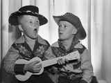 1950s 2 Juvenile Boys in Cowboy Hat and Shirts Playing Ukulele and Singing Mouth Open Wide Photographic Print by D. Corson