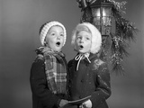 1960s Boy and Girl Singing Christmas Carol Together under Snowy Outdoor Porch Light Photographic Print by H. Armstrong Roberts