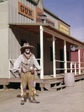 1960s Sad Clown in Cowboy Costume Standing in Street of Western Frontier Town Photographic Print by D. Corson