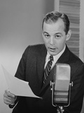 Serious Man Speaking into Microphone Holding Papers Newsman Announcer Broadcaster Photographic Print by H. Armstrong Roberts