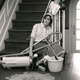 1960s-1970s Exhausted Housewife Sitting at Bottom of Stairs Surrounded by House Cleaning Equipment Photographic Print by H. Armstrong Roberts