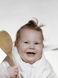 1960s-1970s Smiling Baby Wearing Bib and Holding Wooden Spoon Photographic Print by D. Corson