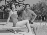 Man Woman Couple Sitting on Diving Board on Side of Swimming Pool Photographic Print by H. Armstrong Roberts