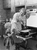1950s Smiling Mother Daughter in Kitchen Broiling Pork Chops Photographie par H. Armstrong Roberts