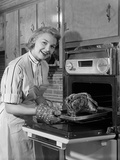 1950s Smiling Woman Housewife Wearing Apron Taking Large Roast Beef from Electric Oven in Kitchen Photographie par H. Armstrong Roberts