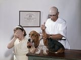 1960s Little Girl Hiding Eyes with as Pet Basset Hound Gets Injection from Veterinarian Photographic Print by D. Corson