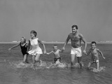 1960s Family Holding Hands Running Together in Water at Seashore Reproduction photographique par H. Armstrong Roberts