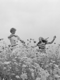 Young Couple Holding Hands Running Through Field of Flowers Photographic Print by H. Armstrong Roberts