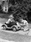 1940s-1930s Boy on Sidewalk Fixing Headlight of Toy Car Driven by Little Girl Playing Outdoor Photographie par H. Armstrong Roberts