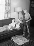 1950s Father on a Sofa with Newspaper While Son Is Standing over Him with Baseball Equipment Photographic Print by D. Corson