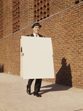 Smiling Man Wearing Suit Necktie and Hat Walking Carrying Large Sandwich Board Photographic Print by H. Armstrong Roberts