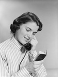 Young Woman Talking on Telephone Reading Address from Little Black Book Photographic Print by H. Armstrong Roberts