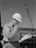 Male Construction Site Supervisor Wearing Hard Hat Reading Papers Photographic Print by H. Armstrong Roberts