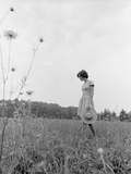 1970s Woman Wearing Dress Carrying Large Straw Hat Standing in Middle of Field Looking Down Photographic Print by H. Armstrong Roberts