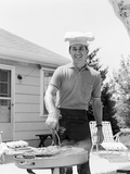 Smiling Man Outdoors in Backyard Patio Wearing Chef Hat Cooking Steaks Hot Dogs on Grill Photographic Print by H. Armstrong Roberts
