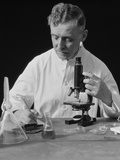Scientist Wearing White Lab Coat Writing Data on Clip Board Holding Focus Control of Microscope Photographic Print by H. Armstrong Roberts