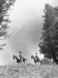 1950s-1960s Two Men on Horseback Riding across Field Wearing Cowboy Hats Photographic Print by D. Corson