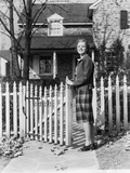 1940s Smiling Pretty Young Teenage Girl Standing by White Picket Fence in Front of Stone House Fotografiskt tryck av H. Armstrong Roberts
