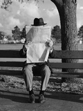Humor Portrait Man Wearing Hat Sitting on Park Bench Reading Newspaper Reproduction photographique par H. Armstrong Roberts