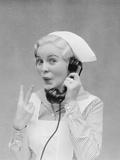 Smiling Blond Nurse with Surprised Expression Talking on Telephone Holding Up Two Fingers Photographic Print by H. Armstrong Roberts