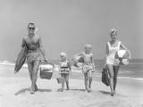 1950s Family of Four Walking Towards Camera with Beach Balls Umbrella Picnic Basket and Sand Bucket Photographie par D. Corson