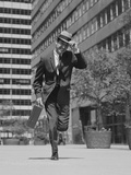 Businessman Carrying Briefcase Holding His Hat on Running Down Urban Sidewalk Photographic Print by H. Armstrong Roberts