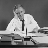 Unhappy Overworked Businessman Sitting at Desk Holding Papers Photographic Print by H. Armstrong Roberts