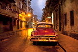 Red Vintage American Car Parked on a Floodlit Street in Havana Centro at Night Fotografisk tryk af Lee Frost