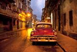 Red Vintage American Car Parked on a Floodlit Street in Havana Centro at Night Fotografisk tryk af Lee Frost