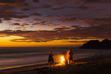 People with Driftwood Fire at Sunset on Playa Guiones Beach Photographic Print by Rob Francis