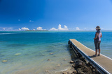 Tourist Standing on a Little Pier with Cocos Island in the Distance Photographic Print by Michael Runkel
