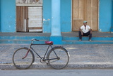 Old Bicycle Propped Up Outside Old Building with Local Man on Steps Photographic Print by Lee Frost