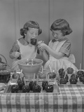 Two Twin Girls Eating Making Candy Apples in Kitchen Photographic Print by H. Armstrong Roberts