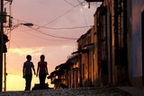 Two Young People in Silhouette at Sunset on Cobbled Street with Colourful Orange Sky Behind Fotografisk tryk af Lee Frost