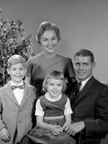 1950s-1960s Family Portrait Smiling Sitting Together in Front of Indoor Christmas Tree Photographic Print