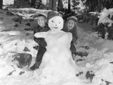 1950s-1960s Smiling Boy and Girl Building a Snowman Together in Snowy Woods Photographic Print