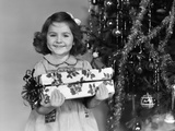 1940s Little Girl Standing Near Christmas Tree Holding a Wrapped Present Smiling Photographic Print