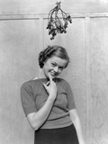 1930s-1940s Cute Young Woman Standing under Mistletoe Smiling Hand Near Mouth Photographic Print