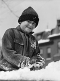1920s-1930s Smiling Boy Playing in Snow Making Snowball Photographic Print