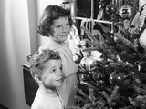 1950s Boy Girl Wearing Pajamas Smiling Up at Christmas Tree Decorations by Window Lámina fotográfica