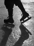 1930s Silhouette Figure Shown from Knees Down Wearing Ice Skates Skating in Ice Sun Glare Photographic Print