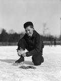 1930s Boy Tying Ice Skate Lace Kneeling on Ice Photographic Print