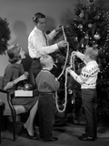 1960s Family Father Mother Two Sons Trimming Christmas Tree with String of Popcorn Photographic Print