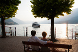 Couple Sitting on Bench and Watching Ferry Approaching Dock Along the Lake Como, Bellagio Photographic Print by Green Light Collection