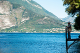 Man Fishing from Dock on Edge of Lake Como, Varenna, Lombardy, Italy Photographic Print by Green Light Collection