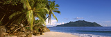Palm Trees Grow Out over a Small Beach with Silhouette Island in the Background, Seychelles Photographic Print