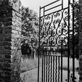 A Decorative Wrought-Iron Gate with Brick Gate Piers Stands Slightly Ajar Photographic Print by John Gay