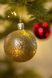 Close-Up of a Golden Hanging Christmas Bauble on Blurred Tree Photographic Print